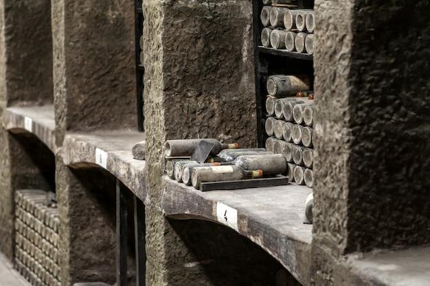 고가의 빈티지 와인 병이 먼지로 덮인 돌 선반