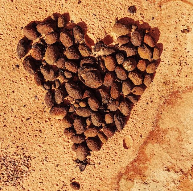 美しい砂岩の山々にハートの形で積み上げられた石。バレンタインデーのコンセプト。