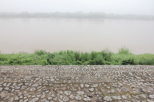 Stone staircase at riverside covered by mist.