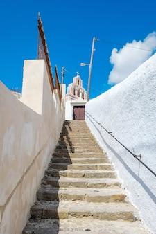 サントリーニ島の青い空と雲の下の石の階段