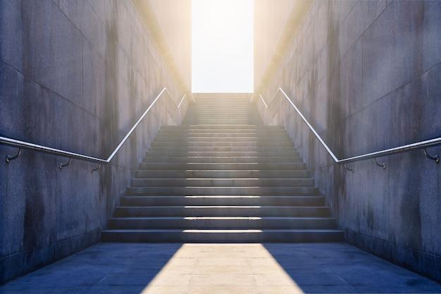 Каменная лестница. подъезд гранитный. червячный свет в двери в конце лестницы. гранитная лестница, ведущая к свету. концепция надежды и светлого будущего.