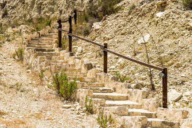 Stone steps and wooden railing between the stones