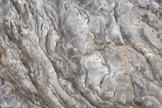 처리되지 않은 회색 shungite, 화강암 또는 대리석의 석재 표면은 강물에서 매끄럽지 만 노년기, 질감의 균열로 덮여 있습니다.