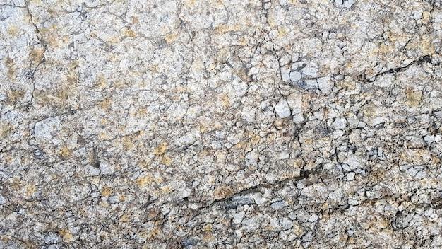 돌 질감 또는 배경입니다. 얼굴의 거친 금이 간 돌 구조. 빈 회색 돌 질감 또는 배경입니다.