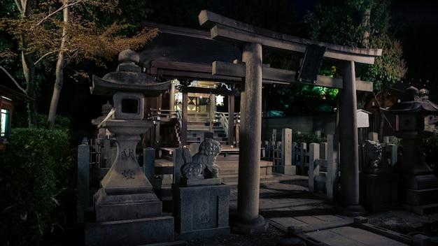 Каменные ворота тории и маленький синтоистский алтарь в храме ясака дзиндзя ночью. храм гион - одна из самых известных святынь киото. япония префектура тотиги город-город со старым входом в тори