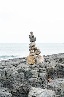 Stone towers on basaltic rocks at hyeopjae beach,jeju island