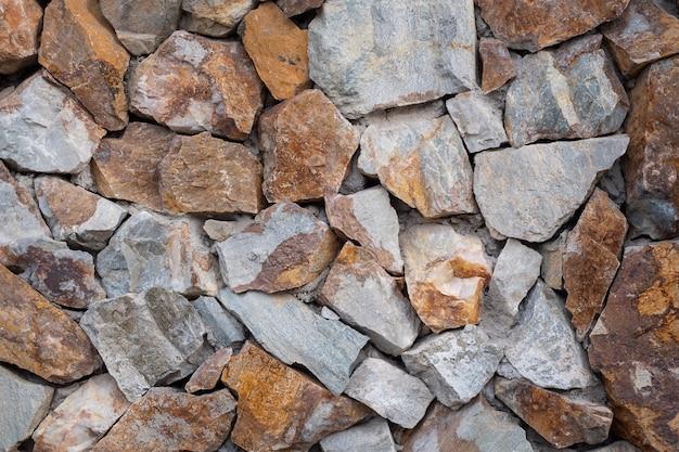 石の壁の背景。灰色、オレンジ色の石からのテクスチャ壁