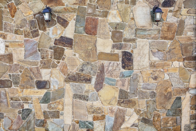 Stone wall in the garden with lamps on the wall. a natural stone.