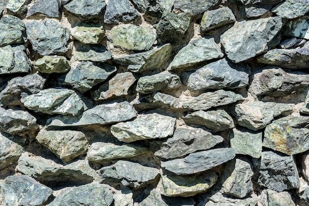 다양한 크기와 색상의 화강암 블록으로 만든 돌담 자연 배경과 질감