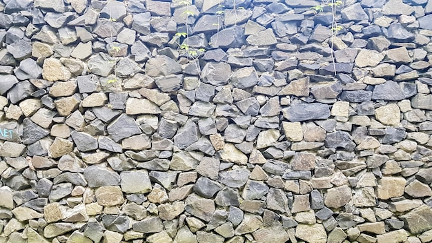 Stone wall texture as background or texture. pattern gray color modern style design decorative uneven cracks real surface.