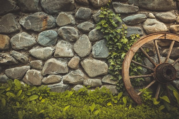 Stone wall texture background. the pattern of old stone wall with ancient wheel and green grass growing. retro vintage toning filter