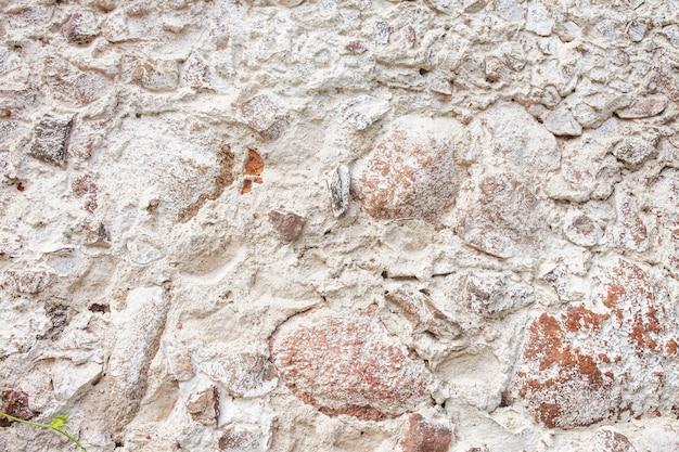 石の壁のテクスチャ。モザイク岩の装飾的な壁の背景。古い石の石積みの壁。家の外壁の装飾面。
