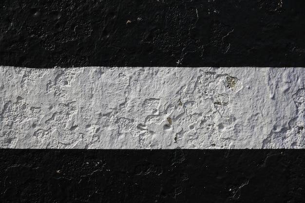 중앙에 은색 줄무늬가 있는 검은색 페인트로 된 돌 벽. 고품질 사진