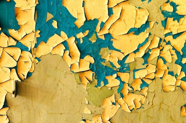 黄色のひびの入った漆喰の石の壁。デザインの背景。グランジテクスチャ。高品質の写真