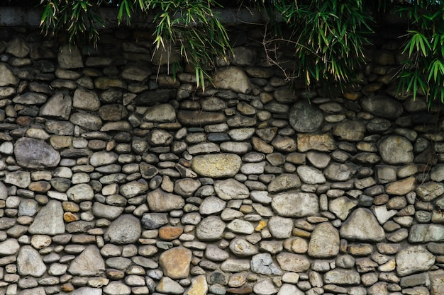 The stone walls are beautiful and have bamboo leaves on top.