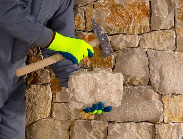 Каменщик каменщик с молотком и камнеобработкой