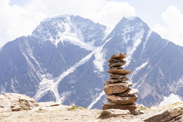 Стоунхендж из маленьких камней на фоне семи ледников на горе донгуз орун и накра тау на эльбрусе, чегет.