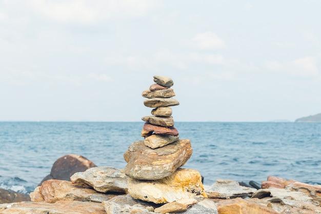 Баланс камней, галька стекают над синим морем в таиланде. голубое небо на солнце летом.