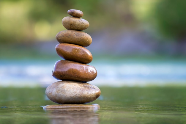 Stones balanced like pile in water.
