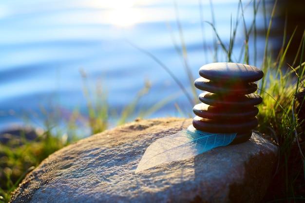 スパの手順のための石は、太陽の光に照らされて、湖の近くの岩の上の山の上にあります