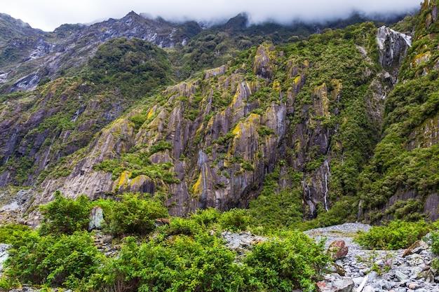 Камни лед и зеленые скалы ледник франца иосифа южный остров новая зеландия
