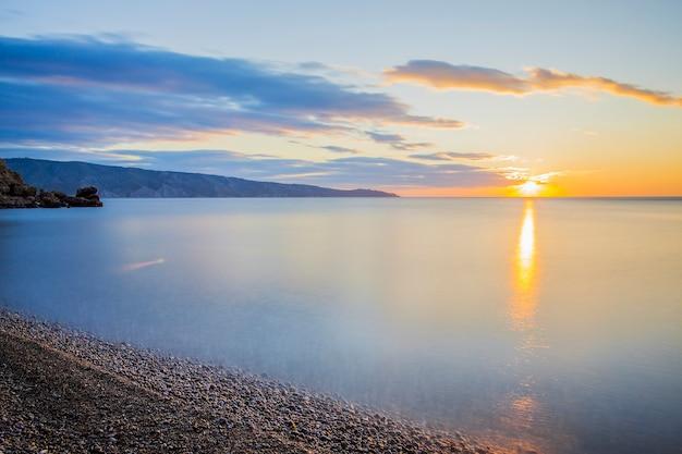 日没に対して海の石、その上に霧。空は雲でいっぱいです。地平線をはるかに超えて山があります