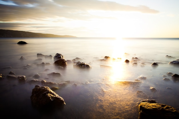 Камни в океане против заката, над которым туман. небо залито облаками. далеко за горизонтом там горы