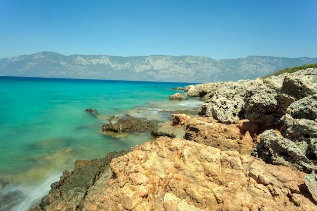 山の景色とぼやけた海を背景に石