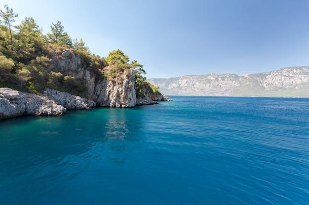 Камни на фоне размытого моря с видом на горы