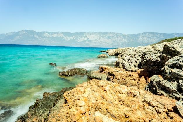 Камни на стене размытого моря с видом на горы