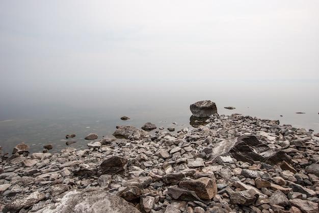 Камни на озере в тумане. туман подобен молоку. скопируйте пространство сверху.