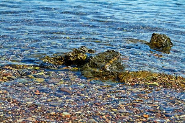 紅海の背景のテクスチャの海岸にある石。イスラエル、エイラート、2018年9月。