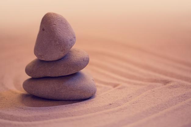 Камни на волнах песчаного фона спа