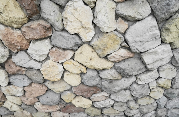 Stones and pebbles on gray wall