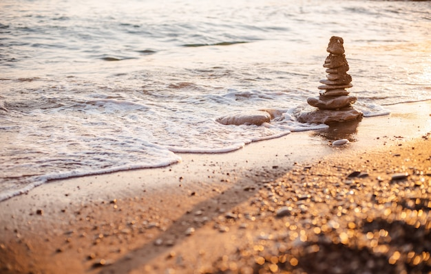 Stones of the pyramid on the beach symbolize the concept of zen