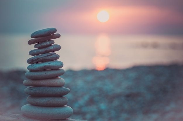 Пирамида из камней на песке, символизирующая дзен, гармонию, равновесие. океан на закате в фоновом режиме.