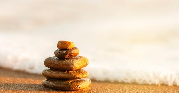 日没時の海岸の石のピラミッド禅の概念
