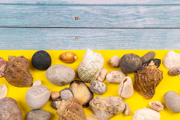 Stones and shells on a blue wooden background and a yellow background.marine theme.