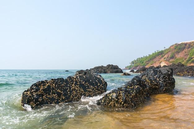 Камни, торчащие из бирюзово-синего моря на фоне скалистого берега. гоа, индия.