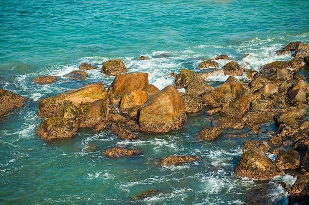 Камни, торчащие из воды моря