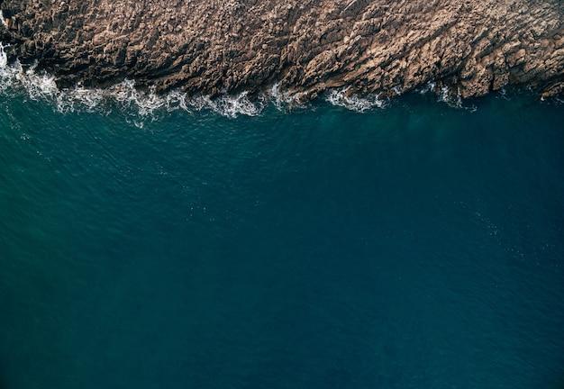 돌 청록색 파도와 바위 공중보기와 대서양 해안선 위에서 바다 거품