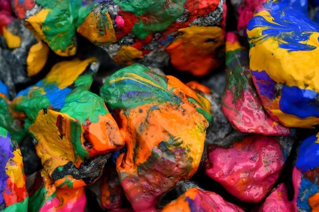 カラフルなペイントの石。さまざまな色でランダムに抽象的な背景色の石