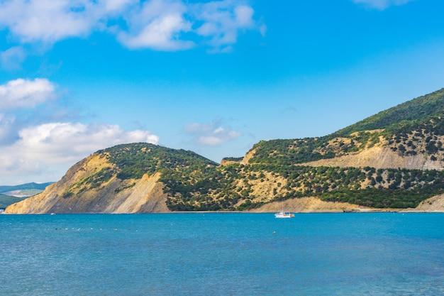 Каменистый пляж побережья черного моря в селе большой утриш, полный людей в яркий солнечный летний день. с высоты птичьего полета.