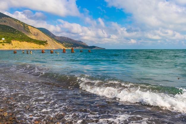 Каменистый пляж черноморского побережья в поселке большой утриш, полный людей ярким солнечным летом