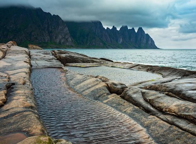 ノルウェー、センジャのエルスフィヨルドにある潮浴のある石のビーチ。夏の極地の昼夜の海岸。竜の歯は遠くまで揺れています。