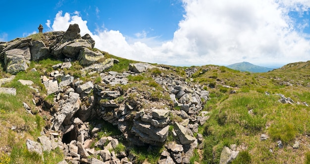 Каменный столб на вершине горы летом и пещера в склоне (украина, карпаты). изображение сшивается четырьмя кадрами.