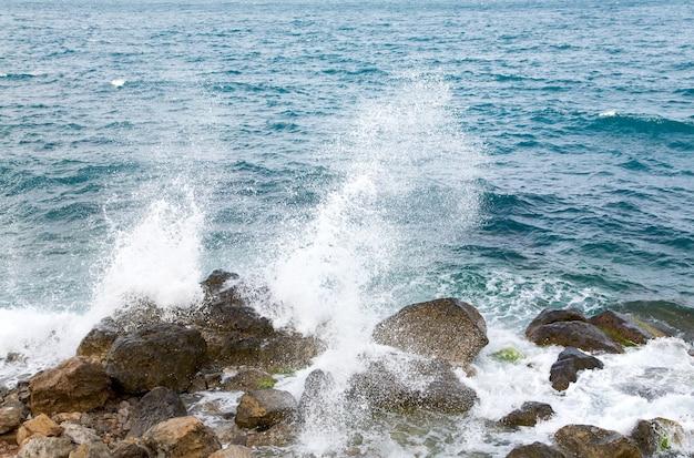 Каменистое морское побережье и волна с вкраплениями
