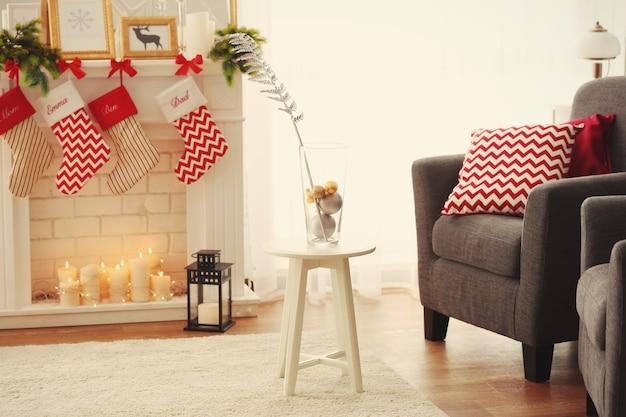 クリスマスのために飾られたリビングルームのガラスの花瓶とスツール