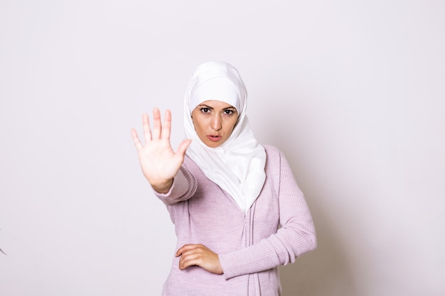 Stop abuse. frightened afro muslim woman in hijab rejecting something with open palm hand gesture