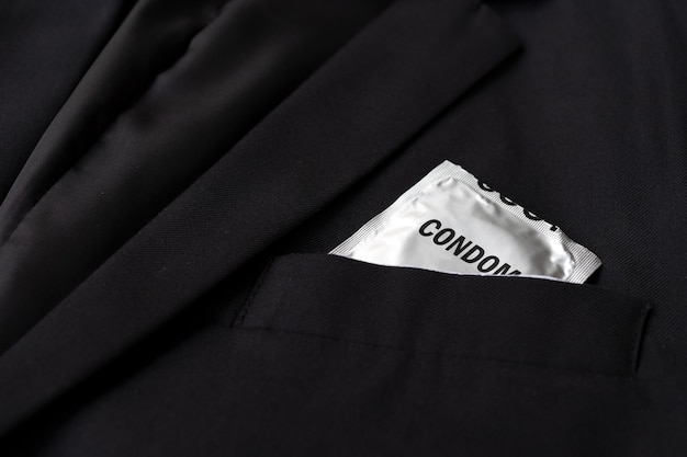 Stop aids and hiv concept. closeup condoms in a black suit background